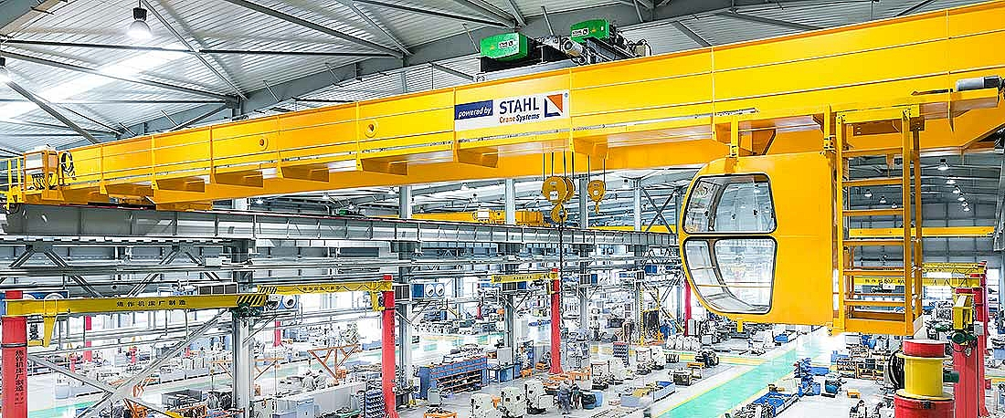 Double girder overhead travelling crane with operator cabin in the production hall.