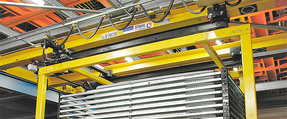 Two coupled STD dual chain hoists with four synchronised load hooks enable low-swing transport of heavy long material.