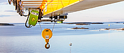 Explosion-proof SH wire rope hoist from STAHL CraneSystems on a slewing crane over the sea.