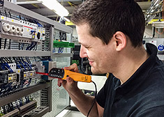 Apprentice electronics technician in industrial engineering checks electrical components in the training lab of STAHL CraneSystems